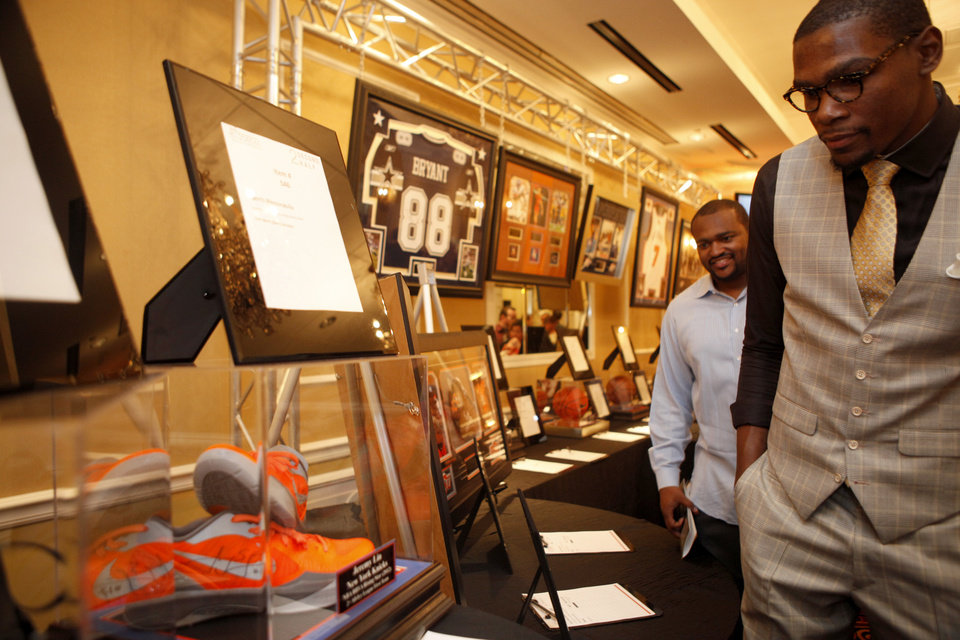 Photo - Oklahoma City's Kevin Durant looks at a pair of shoes autographed by the New York Knick's Jeremy Lin during a silent auction at  the KD 35 Ball benefiting the Kevin Durant Family Foundation at the Skirvin Hilton Hotel in Oklahoma City, Saturday, March 31, 2012. (AP Photo/The Oklahoman, Sarah Phipps) ORG XMIT: OKOKL102