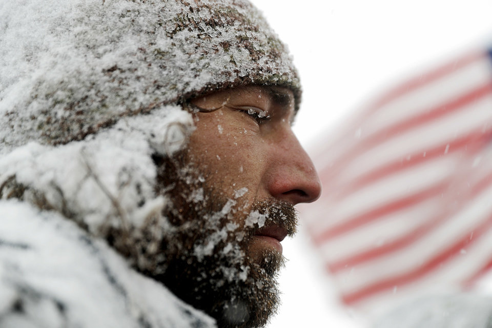Photo - United States Navy veteran John Smeeton, of Chicago, is covered in snow during a march outside the Oceti Sakowin camp where people have gathered to protest the Dakota Access oil pipeline in Cannon Ball, N.D., Monday, Dec. 5, 2016. (AP Photo/David Goldman)