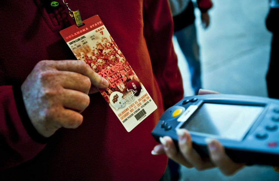 Photo - A Cowboy fan has his pass scanned as he enters the stadium for the Bedlam college football game between the University of Oklahoma Sooners (OU) and the Oklahoma State University Cowboys (OSU) at Boone Pickens Stadium in Stillwater, Okla., Saturday, Nov. 27, 2010. Photo by Chris Landsberger, The Oklahoman
