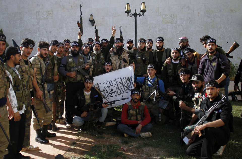 """Photo - In this Wednesday, Nov. 14, 2012 photo, Syrian commander, Mustafa Filfileh, top center, with fighters of """"The Beloved of Allah,"""" brigade pose for a photograph before fighting with government forces on the outskirts of Aleppo. The Beloved of Allah began with ten men, five rifles, one rickety machine gun and a few rocket-propelled grenades soon discovered to be duds. It was born in Maaret Misreen, a town where tractors nearly outnumber cars between the provincial capital of Idlib and the Turkish border to the north. Their leader, 35-year-old Mustafa Filfileh, had no military experience and little idea how to face one of the Mideast's strongest armies. He didn't even know how to drive. They learned fast. In November, the brigade called """"The Beloved of Allah"""" braced for its biggest challenge yet, one that would make clear how far its members had come and how far the war had brought them from their former lives. (AP Photo/ Khalil Hamra)"""