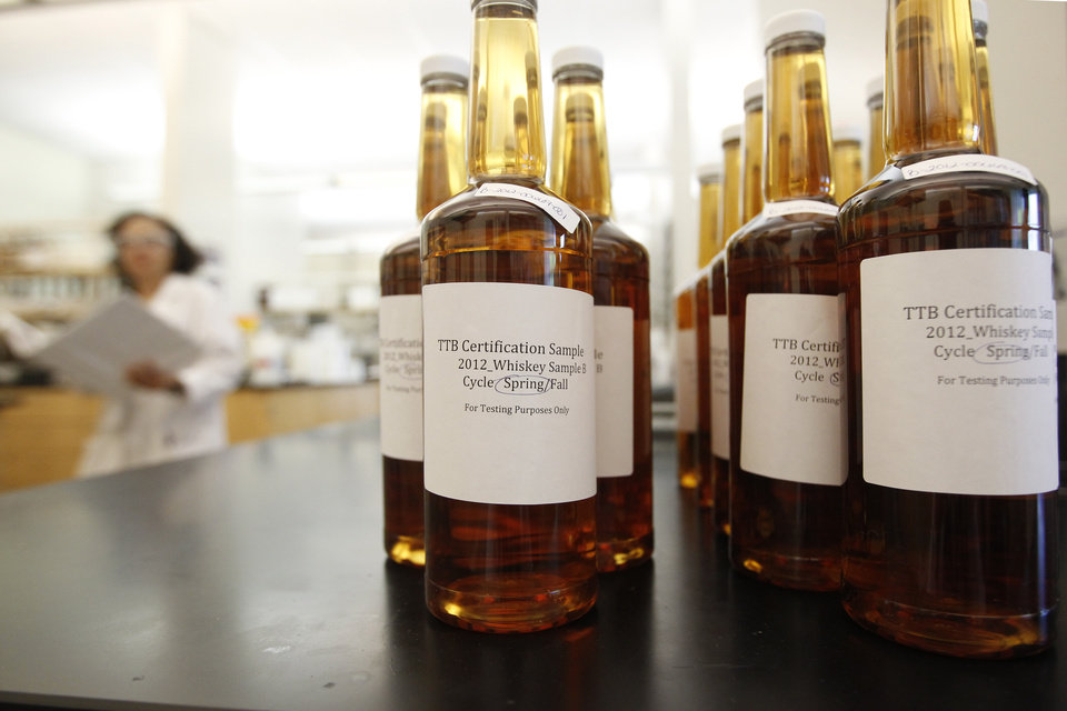 Photo - In this Thursday, April 19, 2012 photo, bottles of whiskey submitted for testing sit at a laboratory operated by the U.S. Department of Treasury's Alcohol and Tobacco Tax and Trade Bureau, in Beltsville, Md. The bureau, which collects taxes on booze and smokes and tells the companies that produce them how to do business, is one example of the specialized government offices threatened by Washington's current zeal for cost-cutting. (AP Photo/Charles Dharapak)