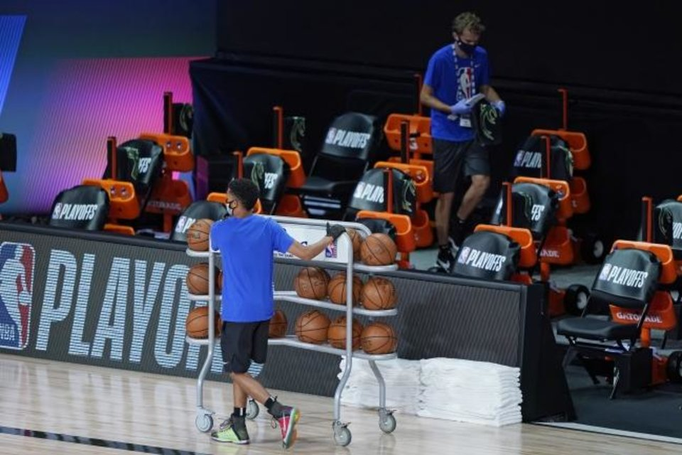 Photo -  Workers clear items from the Milwaukee Bucks bench after the scheduled start time of an NBA playoff game against the Orlando Magic on Wednesday in Lake Buena Vista, Fla. [AP Photo/Ashley Landis, Pool]