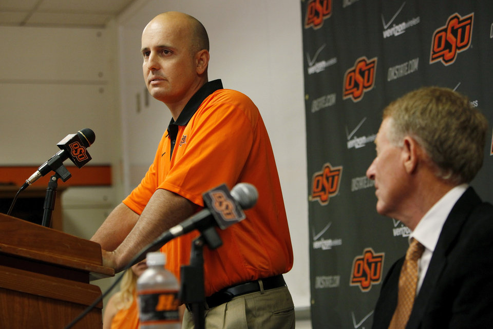 Photo - Josh Holliday speaks as OSU athletics director Mike Holder, right, looks on during a press conference at Oklahoma State University to introduce Josh Holliday as OSU's new head baseball coach, in Stillwater, Okla., Friday, June 8, 2012. Photo by Nate Billings, The Oklahoman