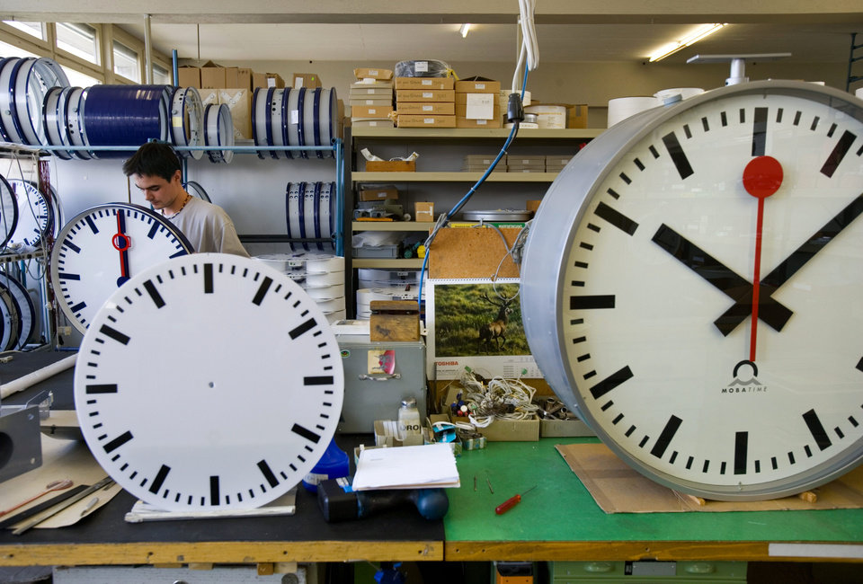 Photo -   FILE - In this Sept. 21, 2005 file photo, an employee at Mobatime Swiss Inc. finishes a Swiss railway station clock at their factory in Sumiswald, Switzerland. Switzerland's national rail company is accusing Apple Inc. of stealing the iconic look of its station clocks for the iOS 6 operating system used on iPad mobile devices. (AP Photo/Keystone, Martin Ruetschi, File)