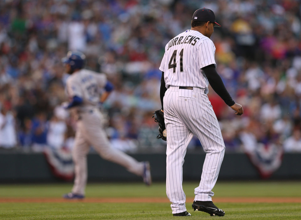 Photo - Colorado Rockies starting pitcher Jair Jurrjns, front, reacts after giving up a three-run home run to Los Angeles Dodgers' Scott Van Slyke, back, in the fifth inning of a baseball game in Denver, Friday, July 4, 2014. (AP Photo/David Zalubowski)