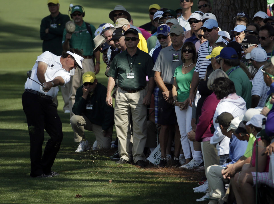 Photo - Spectators watch as Phil Mickelson hits out of the rough on the second fairway during the second round of the Masters golf tournament Friday, April 11, 2014, in Augusta, Ga. (AP Photo/Chris Carlson)