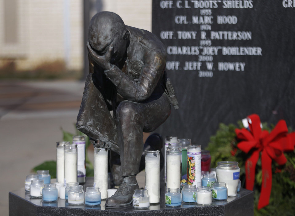 Photo - Candles accumulate for fallen officers who were fatally shot as they investigated a suspicious vehicle, at a police memorial outside the law enforcement center in Topeka, Kan., Monday, Dec. 17, 2012. A suspect in the killings is dead after a nearly two-hour armed standoff, authorities said Monday. (AP Photo/Orlin Wagner)
