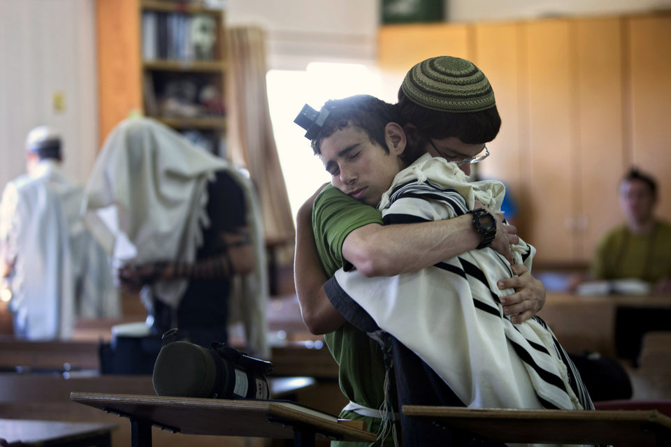 Photo - Israeli Jewish religious students hug prior to a prayer at the synagogue where two of the missing Israeli teens studied, in the Jewish settlement of Kfar Etzion, Sunday, June 15, 2014. Israeli security forces searched the West Bank for a third day Sunday, looking for three missing teenagers, including an American, who they fear have been abducted by Palestinian militants. (AP Photo/Sebastian Scheiner)
