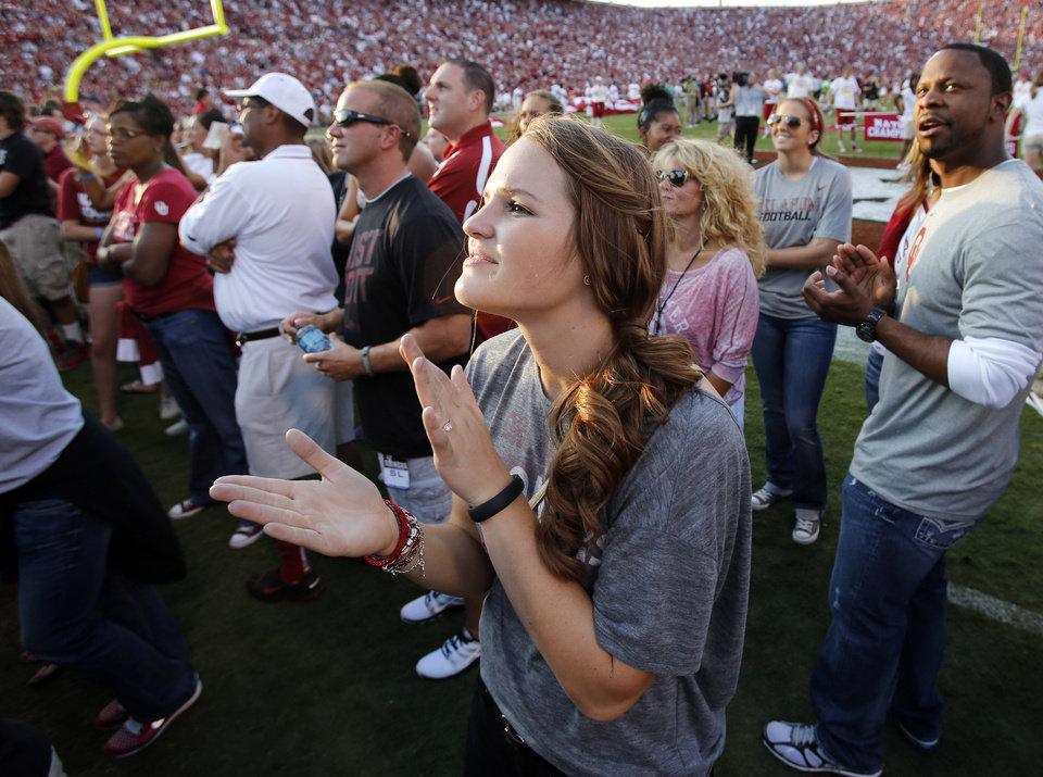 Whitney Hand applauds the introduction of her quarterback husband before a college football game between the University of Oklahoma Sooners (OU) and the Kansas State University Wildcats (KSU) at Gaylord Family-Oklahoma Memorial Stadium, Saturday, September 22, 2012. Photo by Steve Sisney, The Oklahoman <strong>STEVE SISNEY - THE OKLAHOMAN</strong>