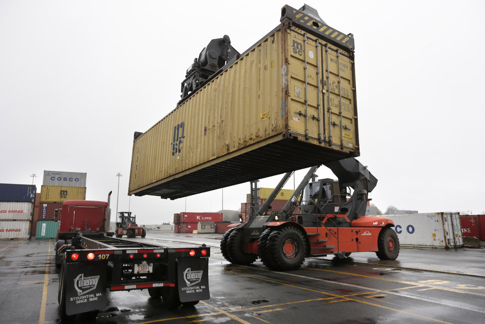 In this photo taken Tuesday, Dec. 18, 2012, a reach stacker operated by a longshoreman, right, places a shipping container on a tractor trailer truck at the Port of Boston, in Boston. The longshoremen\'s union may strike if they are unable to reach an agreement on their contract that expires Dec. 29, 2012. (AP Photo/Steven Senne)