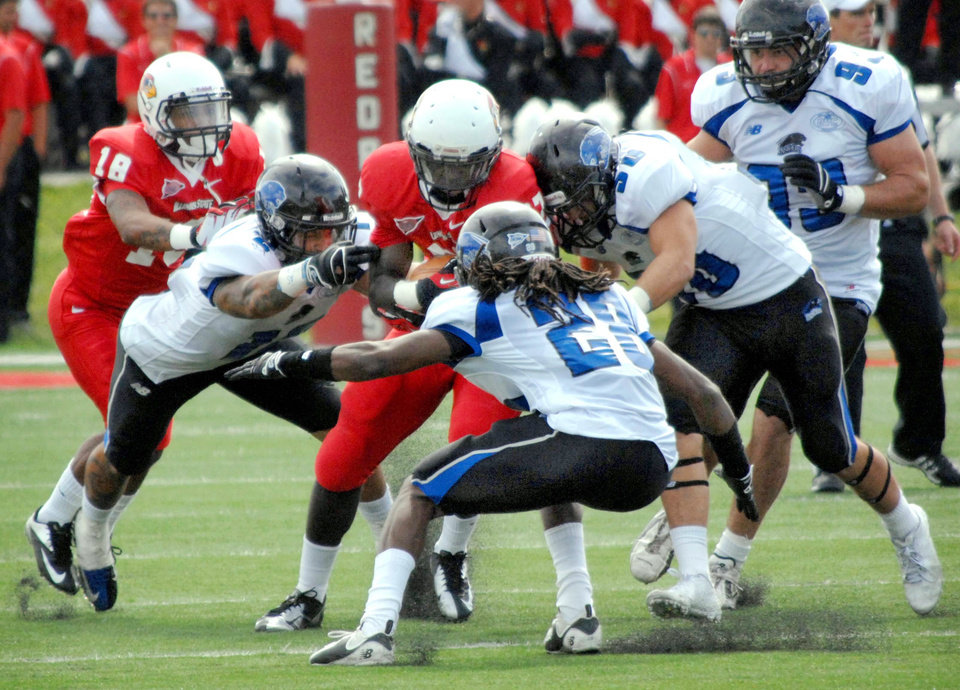 Photo -   Illinois State's Darrelynn Dunn is swarmed by Eastern Illinois University defenders, from left, LeQuince McCall, Nick Beard and Adam Gristick during the first half of during an NCAA college football game Saturday, Sept. 15, 2012, in Normal, Ill. Illinois State won 54-51 in two overtimes. (AP Photo/The Pantagraph, Steve Smedley) (AP PHOTO The Pantagraph/STEVE SMEDLEY)