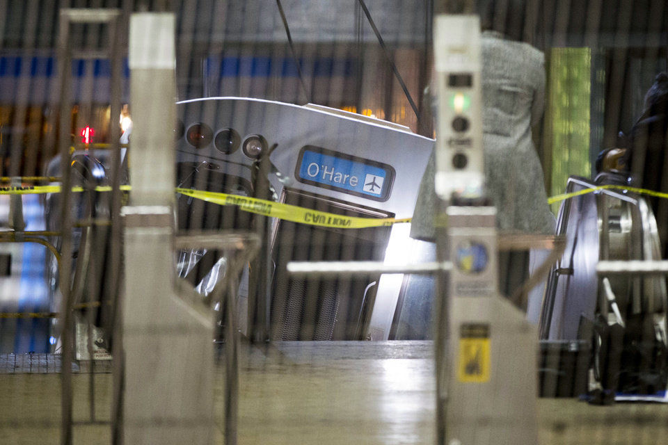 Photo - A derailed Chicago Transit Authority train car rests on an escalator at the O'Hare Airport station early Monday, March 24, 2014, in Chicago. More than 30 people were injured after the eight-car train plowed across a platform and scaled the escalator at the underground station. (AP Photo/Andrew A. Nelles)