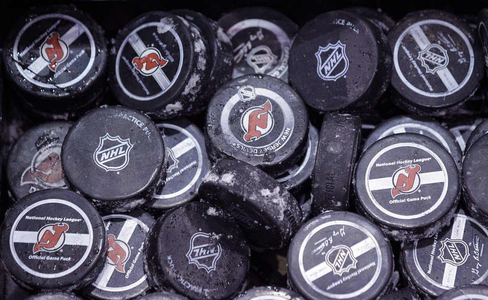 FILE - In this May 15, 2012, file photo, ice covered hockey pucks are shown at the New Jersey Devils practice rink in Newark, N.J. The NHL said Thursday, Oct. 4, 2012, that it has canceled the hockey season through Oct. 24, a total of 82 games, because of the ongoing lockout. The NHL and the players\' union are unable to decide how to divide $3 billion in hockey-related revenues. There have been negotiations in recent days, but the sides have not gotten any closer to an agreement on core economic issues.(AP Photo/Julio Cortez, File)