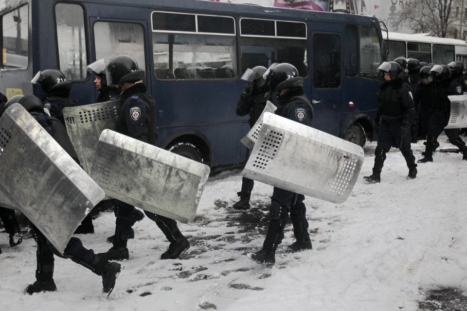 Riot police officers leave their bus to block Pro-European Union activists gathered at the Independence Square in KIev, Ukraine, Monday, Dec. 9, 2013. The policemen, wearing helmets and holding shields, formed a chain across Kiev�s main street outside the city building. Organizers called on protesters to vacate the city hall and the other building which the opposition had used as its headquarters. (AP Photo/Sergei Chuzavkov)