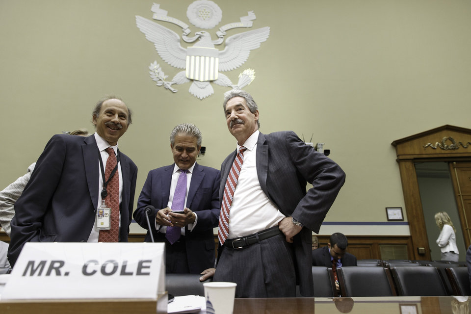 Photo - Deputy Attorney General James Cole, right, arrives on Capitol Hill in Washington, Thursday, July 17, 2014, to testify before the House  Economic Growth, Job Creation, and Regulatory Affairs subcommittee hearing on how the Justice Department is investigating allegations that the Internal Revenue Service (IRS) targeted conservative political groups for extra scrutiny.   (AP Photo/J. Scott Applewhite)