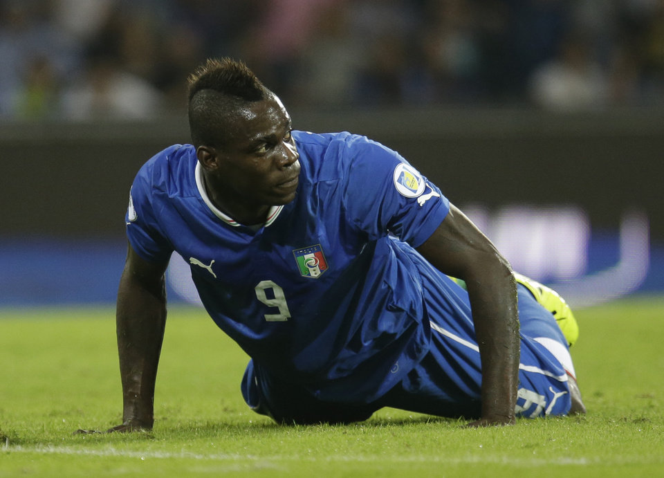 Photo - FILE - In this Oct. 15, 2013, file photo, Italy's Mario Balotelli lies on the pitch during a 2014 FIFA World Cup, Group B, qualification match between Italy and Armenia in Naples, Italy. Italy's intentions will likely depend on the wavering ways of talented forward Mario Balotelli, whose mood swings often get him into trouble both on and off the field. (AP Photo/Gregorio Borgia, File)