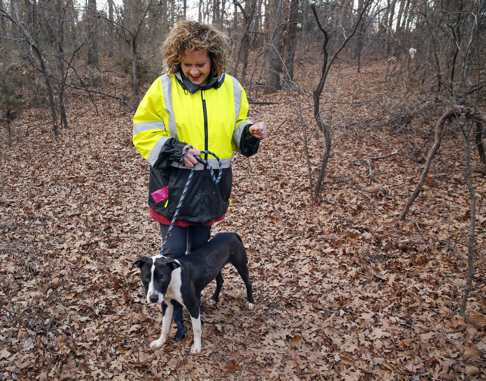 Photo -  Volunteer supervisor Deb O'Day works with rescue dog Colt on the walking trails at the Edmond Animal Shelter. [PHOTO BY NATE BILLINGS, THE OKLAHOMAN]