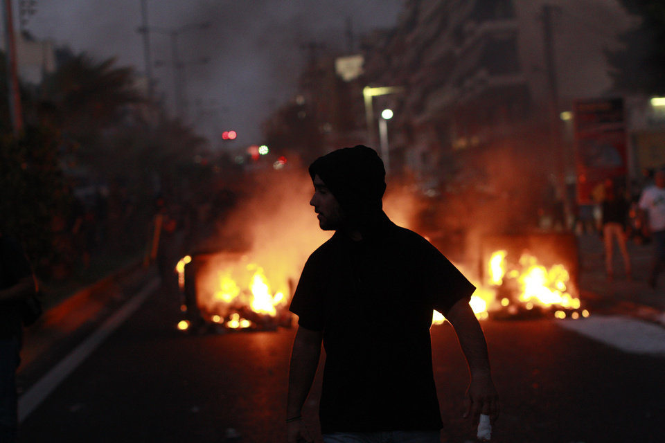 A protester walks in front of a burning barricade, during a protest after the stabbing of a 34 year old man in the suburb of Keratsini near Athens , Wednesday, Sept. 18 2013.  Violent clashes broke out Wednesday in several Greek cities after a member of the country�s far-right Golden Dawn party was arrested in the fatal stabbing of a 34-year-old musician described as an anti-fascist activist. The stabbing drew condemnation from across Greece�s political spectrum and from abroad. While the extremist Golden Dawn has been blamed for numerous violent attacks in the past, the overnight stabbing is the most serious violence directly attributed to a member so far. (AP Photo/Kostas Tsironis)