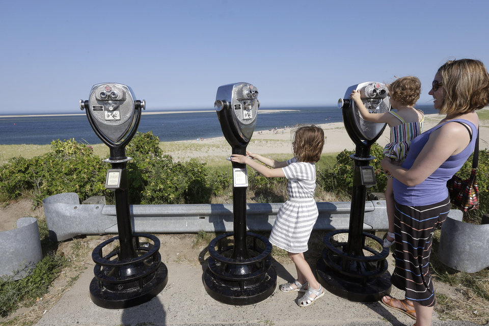 Photo - In this July 2, 2014 photo, Molly Saint-James, of Baltimore, right, helps her daughters Ellie McDonald, left, 6, and Poppy McDonald, 3, use telescopic viewers overlooking a beach while on vacation in Chatham, Mass. Growing sightings of great white sharks off Cape Cod are generating business for local entrepreneurs as residents and tourists seek get a glimpse of the offshore predators -- and purchase their shark-themed memorabilia. (AP Photo/Steven Senne)