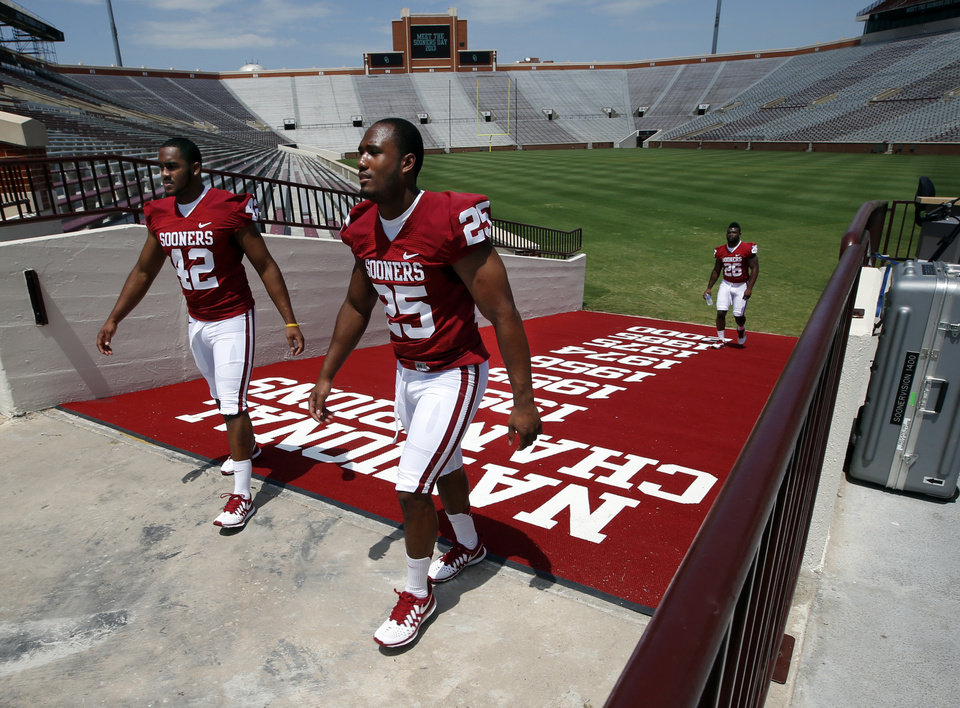Photo - Dominique Alexander, (42), Aaron Franklin (25), and Damien Williams (26) head to Sooner Vision Studios during media access day for the University of Oklahoma Sooner (OU) football team in the Adrian Peterson meeting room in Gaylord Family-Oklahoma Memorial Stadium in Norman, Okla., on Saturday, Aug. 3, 2013. Photo by Steve Sisney, The Oklahoman