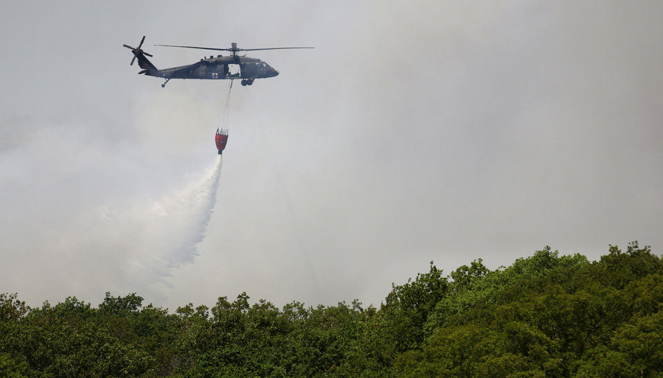 Photo - An Oklahoma National Guard helicopter drops water on a wildfire Monday in Logan County.  Photos By Steve Gooch, The Oklahoman  Steve Gooch