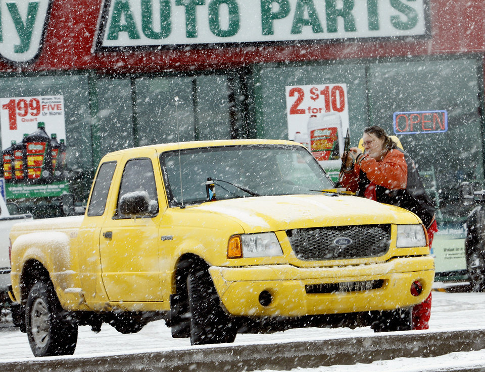 Photo - A motorist puts new wiper blades on her pickup on Friday, Jan. 29, 2010, in Purcell, Okla.  A winter storm knocked power out to much of the town Thursday and Friday.  Photo by Steve Sisney, The Oklahoman