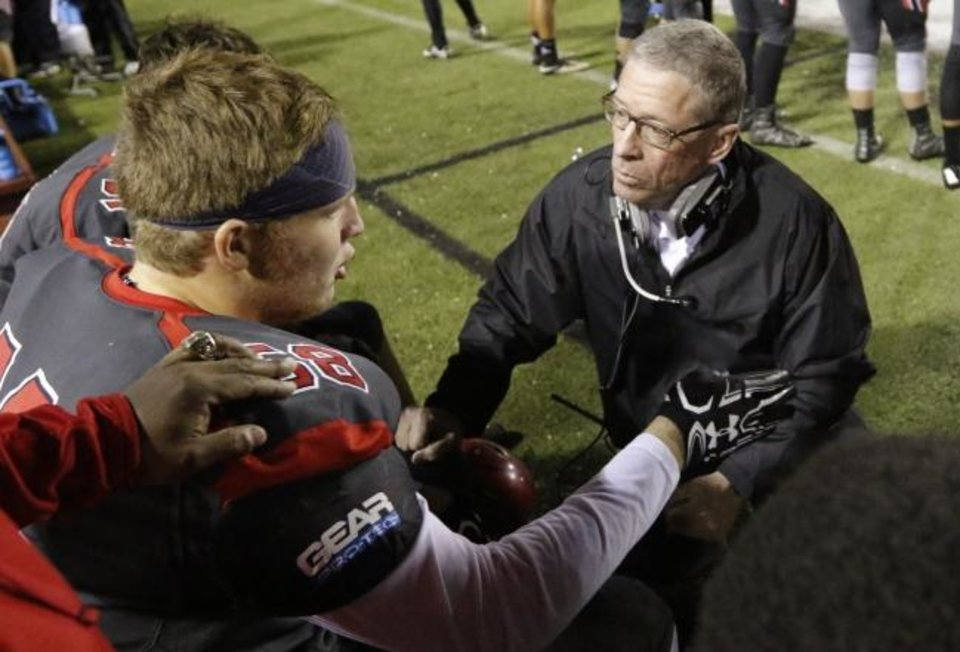 Photo -  Carl Albert coach Gary Rose talks with Trey Forbes on the sideline during a Class 5A state playoff game in 2016. Rose built a special relationship with his players and coaches over the 22 years he spent as the Titans' head coach. [Steve Sisney/The Oklahoman]