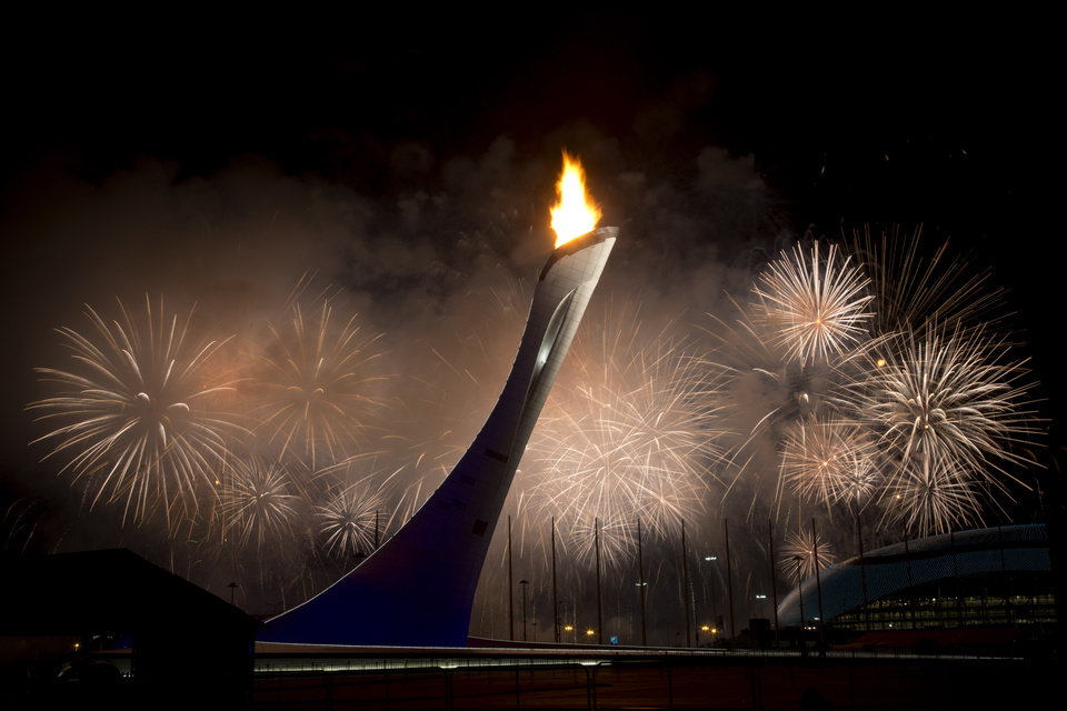 Photo - Fireworks explode behind the Olympic torch after it was lit at end of the opening ceremony for the 2014 Winter Olympics in Sochi, Russia, Friday, Feb. 7, 2014. (AP Photo/Bernat Armangue)