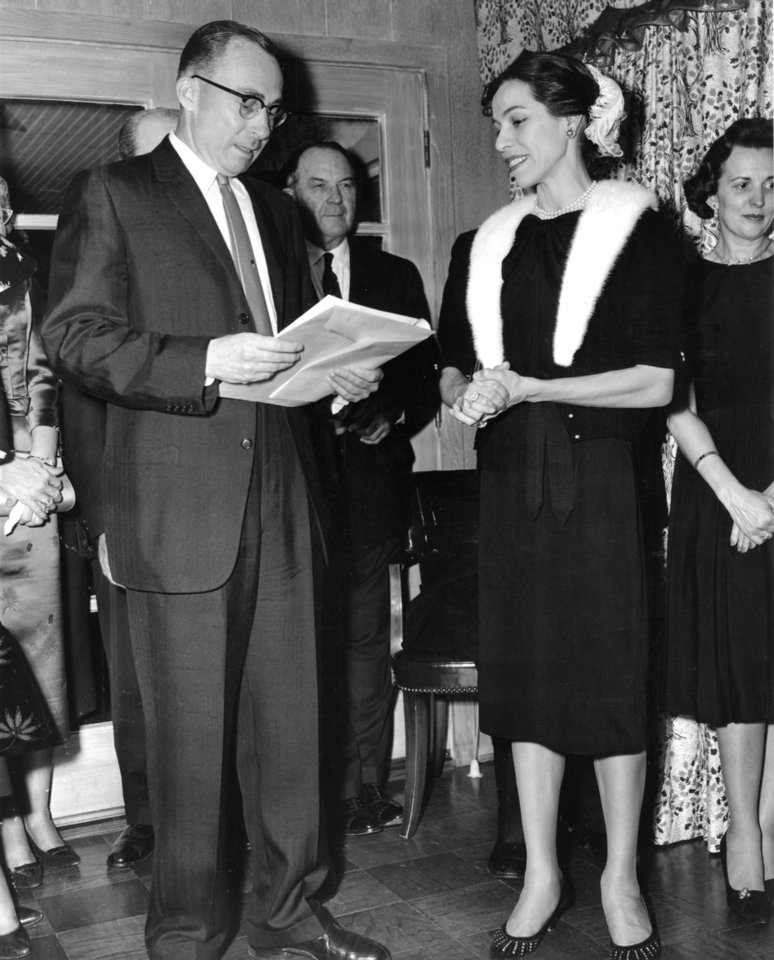 BALLERINAS: Oklahoma Indian ballerina Maria Tallchief (right) listens to citation read by Oklahoma City Chamber of Commerce president E.L. Gaylord (left) during presentation of a sculptured bronze portrait of Miss Tallchief to Miss Tallchief Saturday night, 1/16/60, in the home of Mr. and Mrs. Guy James. Tallchief was in OKC to dance with the Oklahoma City Symphony at 3 p.m Sunday, 1/17/60, in the Muncipal Auditorium. Staff photo by Richard