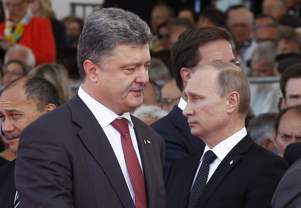 Photo - Ukraine's President-elect Petro Poroshenko, left, walks past Russian President Vladimir Putin during the commemoration of the 70th anniversary of the D-Day in Ouistreham, western France, Friday, June 6, 2014. World leaders and veterans gathered by the beaches of Normandy on Friday to mark the 70th anniversary of World War Two's D-Day landings. (AP Photo/Christophe Ena, Pool)