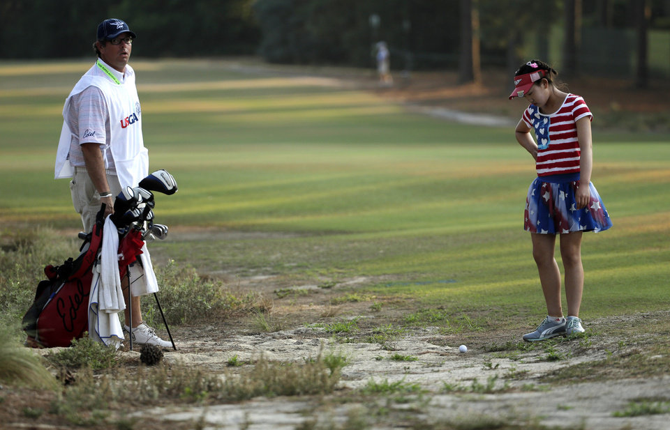 Photo - Lucy Li checks out her lie in the waste area on the 11th fairway during the first round of the U.S. Women's Open golf tournament in Pinehurst, N.C., Thursday, June 19, 2014. Looking on is her caddie Bryan Bush. (AP Photo/Chuck Burton)