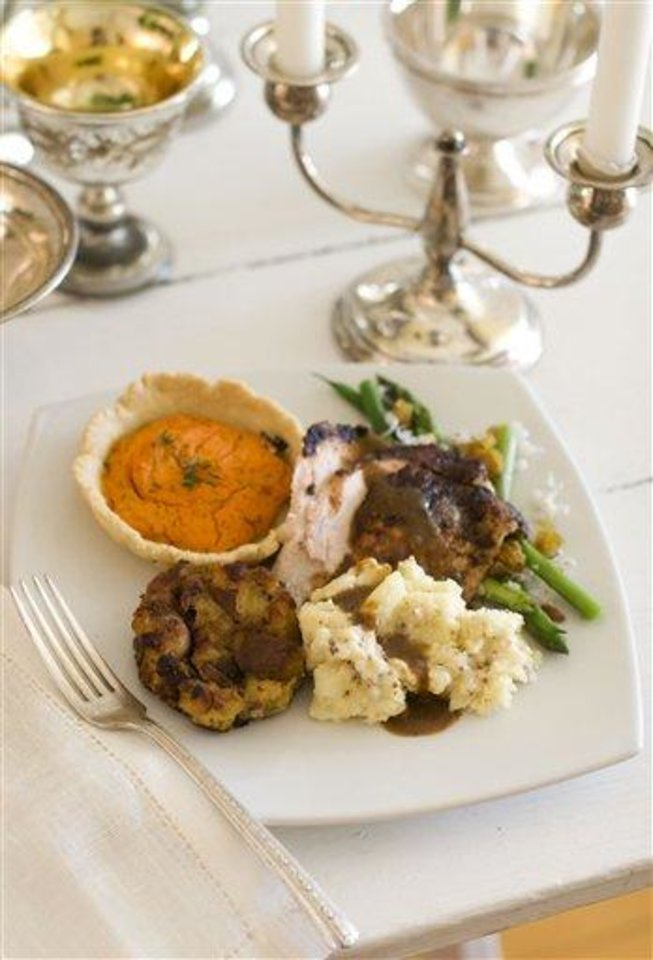 In this image taken on October 22, 2012, a gourmet Thanksgiving dinner of porcini soy turkey with shallot truffle gravy, pan fried cranberry pancetta stuffing, asparagus and haricots verts with goat cheese and pine nuts, lemon-herb carrot tarts, handmade mustard butter and buttermilk mashed potatoes is shown served on a plate in Concord, N.H. (AP Photo/Matthew Mead)