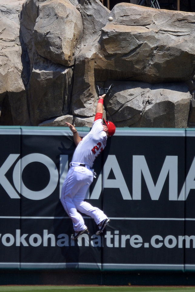 Los Angeles Angels center fielder Mike Trout cannot reach a ball hit for a solo home run by Houston Astros' L.J. Hoes during the first inning of a baseball game on Sunday, Aug. 18, 2013, in Anaheim, Calif. (AP Photo/Mark J. Terrill)