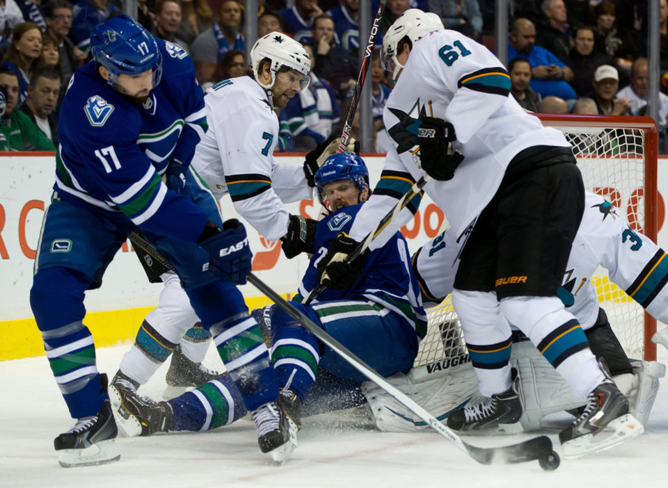 Vancouver Canucks' Ryan Kesler, left, attempts a shot on San Jose Sharks' goalie Antti Niemi, of Finland, as Brad Stuart, 7, and Justin Braun, 61, check Canucks Daniel Sedin, center, of Sweden, during the first period of an NHL hockey game, Thursday, Nov. 14, 2013 in Vancouver, British Columbia.  (AP Photo/The Canadian Press, Darryl Dyck)