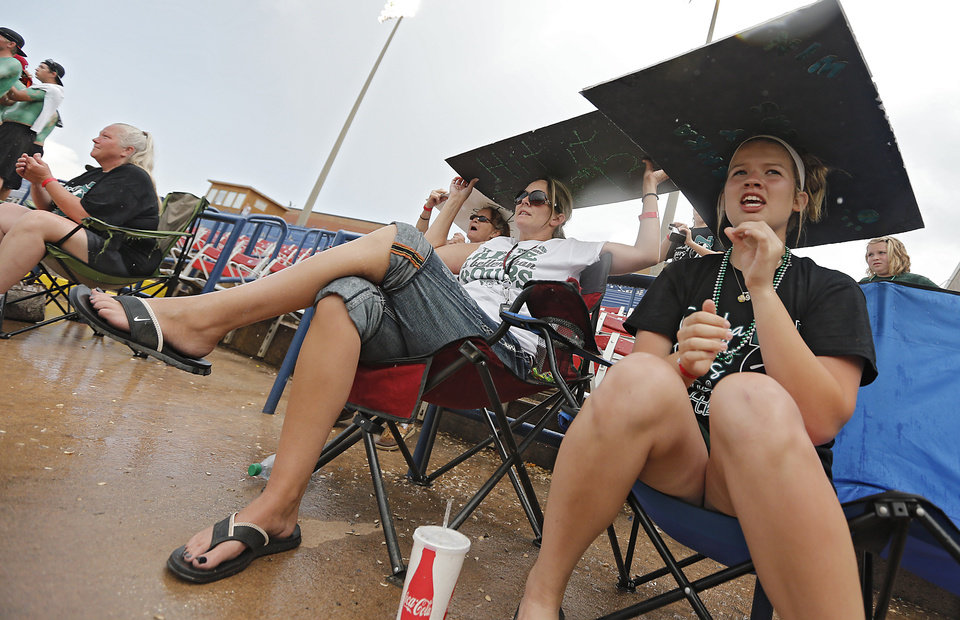 Tushka fans Christy Eaves and Emily Nutt, from left, brave the rain as they cheer on their team in the Class 4A Oklahoma State High School Slow Pitch Softball Championship at ASA Hall of Fame Stadium in Oklahoma City, Wednesday, May 1, 2013. Photo by Chris Landsberger, The Oklahoman