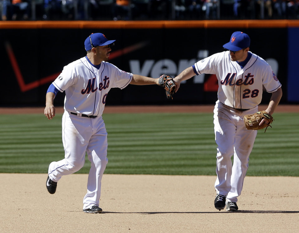Photo - New York Mets shortstop Omar Quintanilla, left, and New York Mets second baseman Daniel Murphy celebrate a double play during the seventh inning of a baseball game against the Atlanta Braves, Sunday, April 20, 2014 in New York. (AP Photo/Seth Wenig)