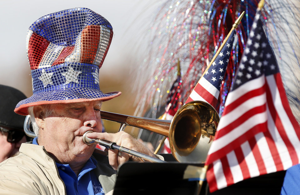 Photo - Wearing a colorful Uncle Sam hat, this man plays the trombone while riding on a float with members of the Flying High Band who entertained the crowds along the route with patriotic tunes and other lively songs during the Midwest City Veteran's Day Parade on Friday, Nov. 10, 2017. Photo by Jim Beckel, The Oklahoman