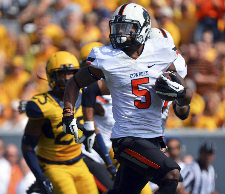Photo - Oklahoma State receiver Josh Stewart (5) runs for 73-yards for a touchdown reception during the first quarter of an NCAA college football game against West Virginia in Morgantown, W.Va., on Saturday, Sept. 28, 2013. (AP Photo/Tyler Evert) ORG XMIT: WVTE105