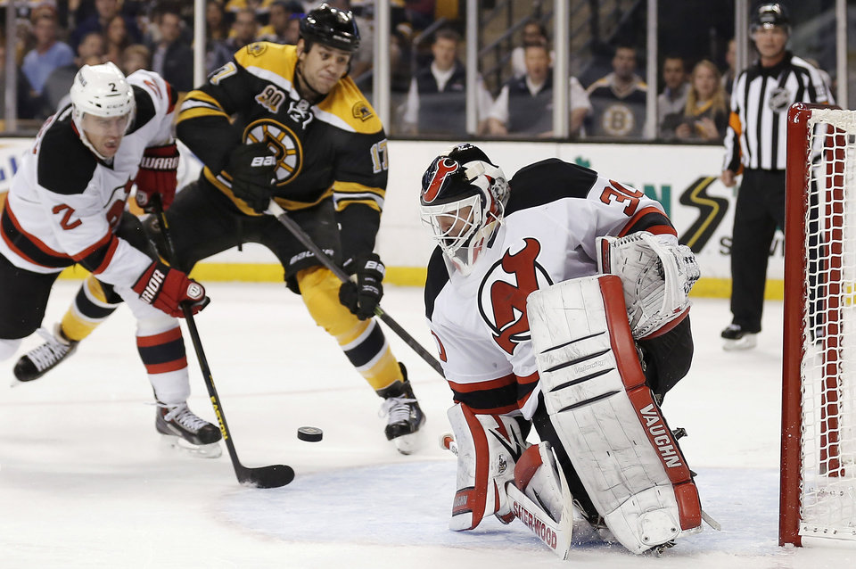 Photo - New Jersey Devils goalie Martin Brodeur, right, makes a save as Boston Bruins' Milan Lucic, center, and Devils defenseman Marek Zidlicky, of the Czech Republic, battle for position during the second period of an NHL hockey game in Boston, Saturday, Oct. 26, 2013. (AP Photo/Winslow Townson)