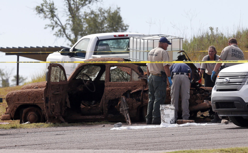 Photo - Law enforcement officials from multiple agencies examine the two cars pulled from Foss Lake, in Foss, Okla., Wednesday, Sept. 18, 2013. The Oklahoma State Medical ExaminerÂ's Office says authorities have recovered skeletal remains of multiple bodies in the Oklahoma lake where the cars were recovered. (AP Photo/Sue Ogrocki) ORG XMIT: OKSO102