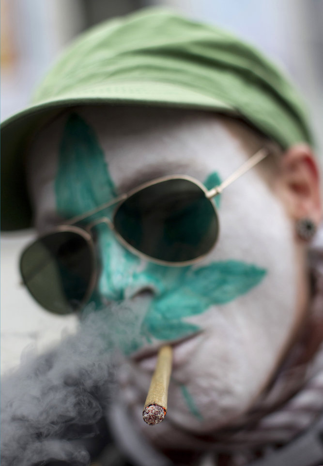 Photo -   FILE - In this Friday April 20, 2012 file photo a protestor from Belgium with a marijuana leaf painted on his face smokes a marijuana joint in Amsterdam during a protest against a government plan to stop foreigners from buying marijuana in the Netherlands. The new Dutch government is scrapping a planned