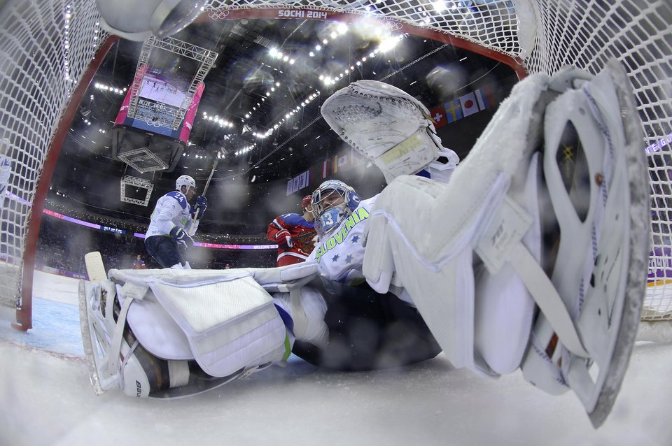 Photo - Slovenia goaltender Robert Kristan falls into the goal against Russia during the third period of a men's ice hockey game at the 2014 Winter Olympics, Thursday, Feb. 13, 2014, in Sochi, Russia. (AP Photo/Bruce Bennett, Pool)