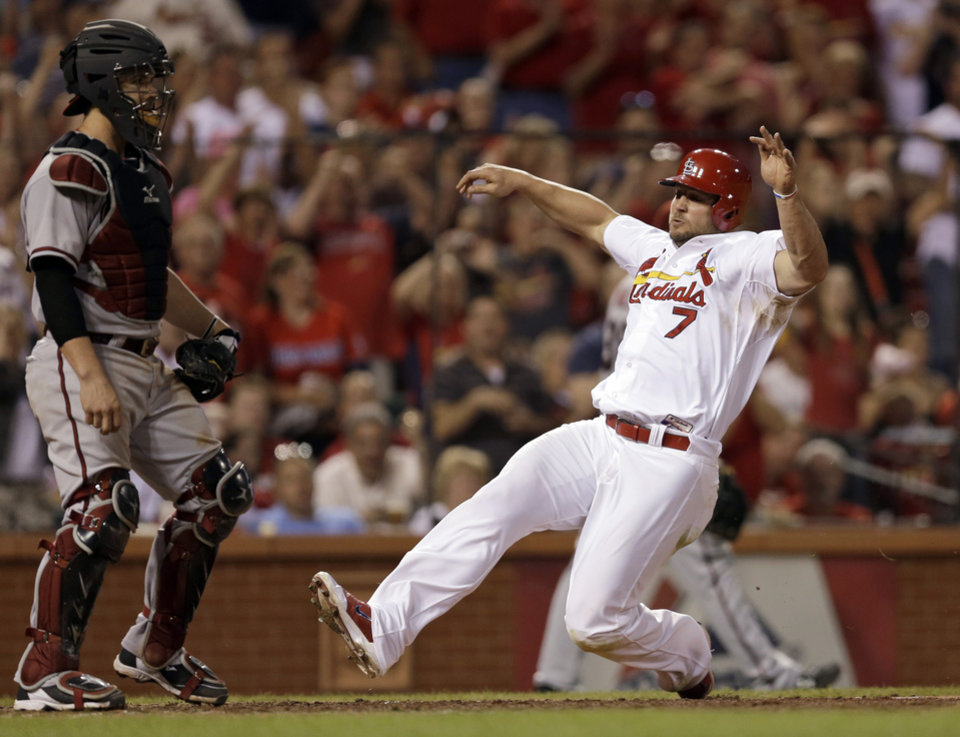 Photo - St. Louis Cardinals' Matt Holliday scores on a double by Allen Craig as Arizona Diamondbacks catcher Tuffy Gosewisch stands by during the seventh inning of a baseball game Thursday, May 22, 2014, in St. Louis. (AP Photo/Jeff Roberson)