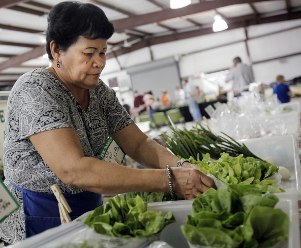Photo - Lita Leatherwood arranges lettuce at her and her husband's booth at the farmer's market on the campus of OSU-OKC on June 5, 2013. Photo by KT KING, The Oklahoman