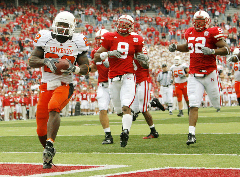 Photo - OSU's Dantrell Savage (22) runs for a touchdown as Nebraska defenders follow, including Bryan Wilson (9) and Phillip Dillard (52), in the fourth quarter during the college football game between Oklahoma State University (OSU) and the University of Nebraska (NU) at Memorial Stadium in Lincoln, Neb., Saturday, October 13, 2007. OSU won, 45-14. By Nate Billings, The Oklahoman