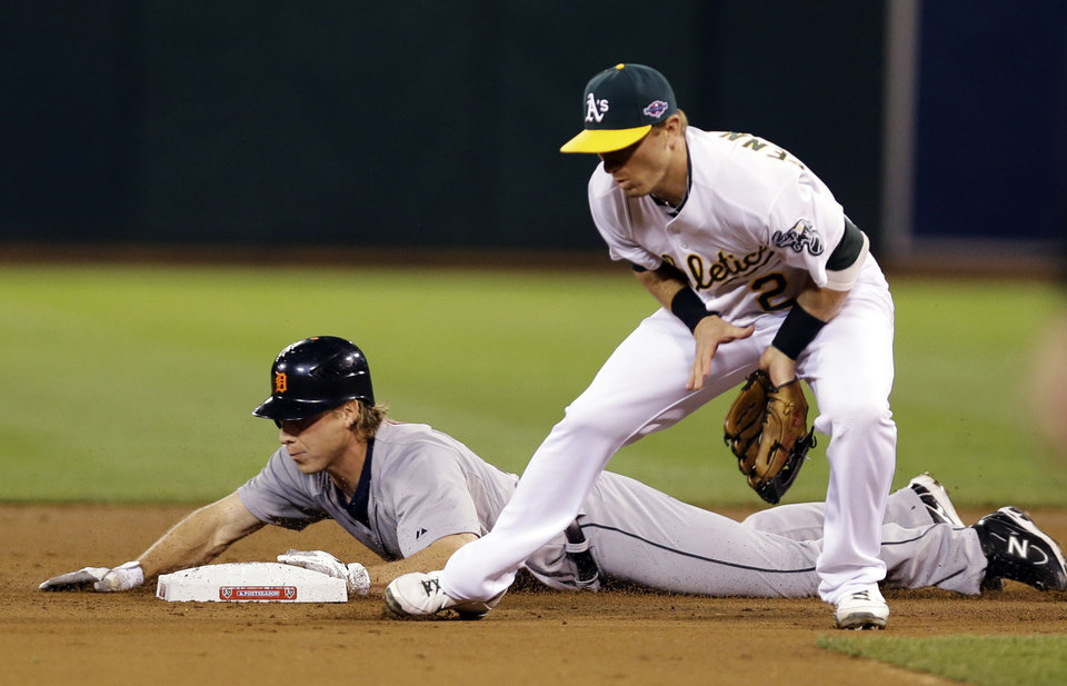 Detroit Tigers' Andy Dirks slides safely into second past Oakland Athletics shortstop Cliff Pennington (2) in the second inning of Game 4 of their American League division baseball series in Oakland, Calif., Wednesday, Oct. 10, 2012. (AP Photo/Marcio Jose Sanchez)