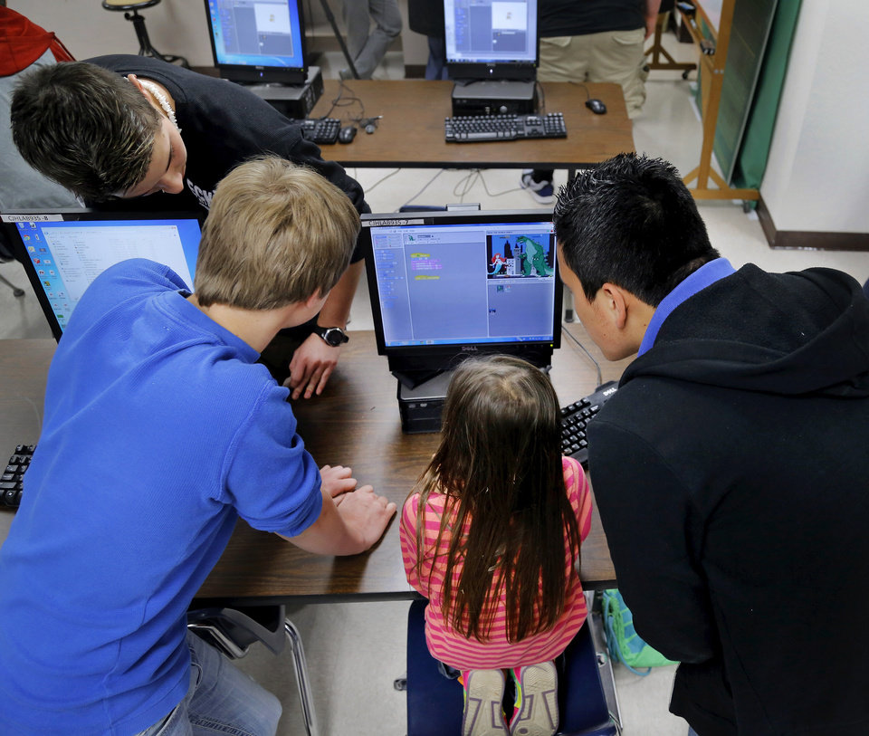 Photo - Second grader Charity Fristad stares at a computer screen as three junior high students gather around to help her. Moore Central Junior High students who are enrolled in video game design classes have created math and language learning games using characters from books their neighbors from Plaza Towers Elementary love to read. Students from both schools will get together on Wednesday, May 14, 2014, to play the games and get an opportunity to experience writing CODE.    Photo by Jim Beckel, The Oklahoman