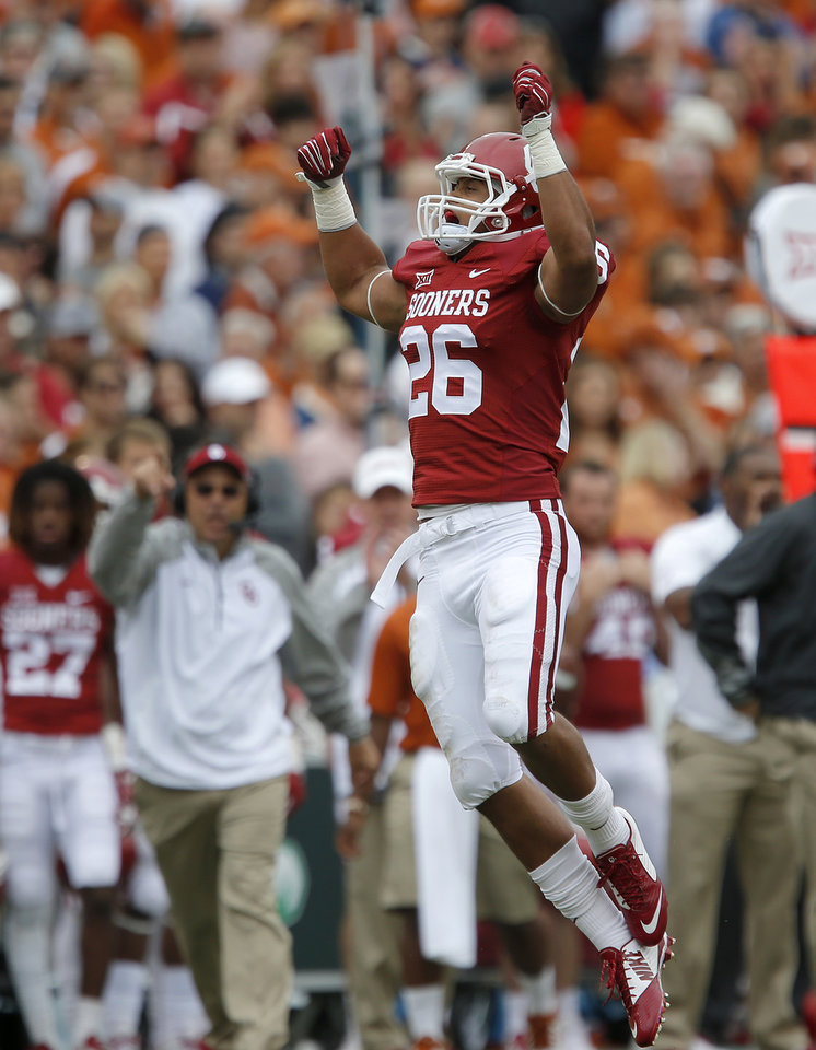 Photo - Oklahoma's Jordan Evans (26) celebrates after a tackle during the Red River Showdown college football game between the University of Oklahoma Sooners (OU) and the University of Texas Longhorns (UT) at the Cotton Bowl in Dallas on Saturday, Oct. 11, 2014. 