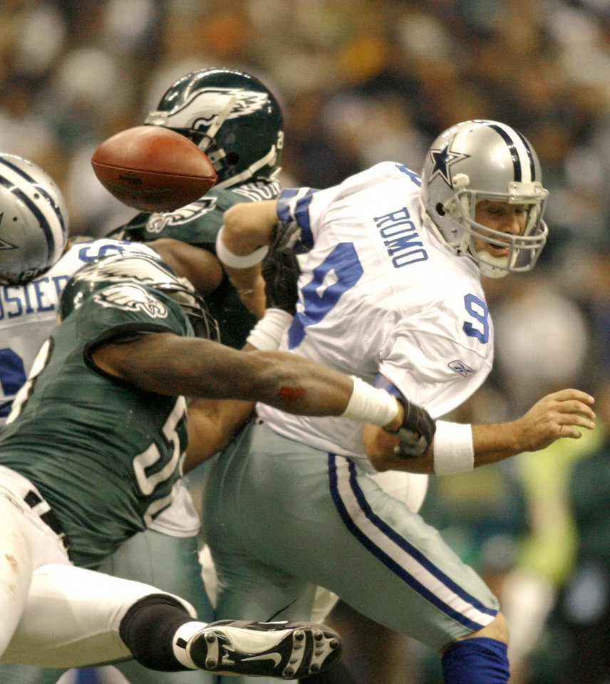Photo - Dallas Cowboys quarterback Tony Romo (9) looses the ball after being hit by Philadelphia Eagles defensive end Trent Cole (58) in the fourth quarter of their NFL football game, Sunday, Dec. 16, 2007, in Irving, Texas. The Cowboys recovered but lost the game 10-6.  (AP Photo/Mike Stone) ORG XMIT: IRV129