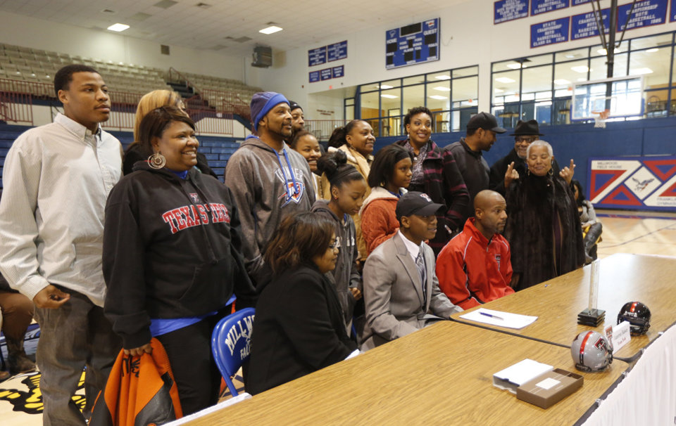 Photo - Millwood's Cameron Batson poses with friends and family members after he signed to play football for Texas Tech during signing day at Millwood High School in Oklahoma City, Wednesday February 05, 2014. Photo By Steve Gooch, The Oklahoman
